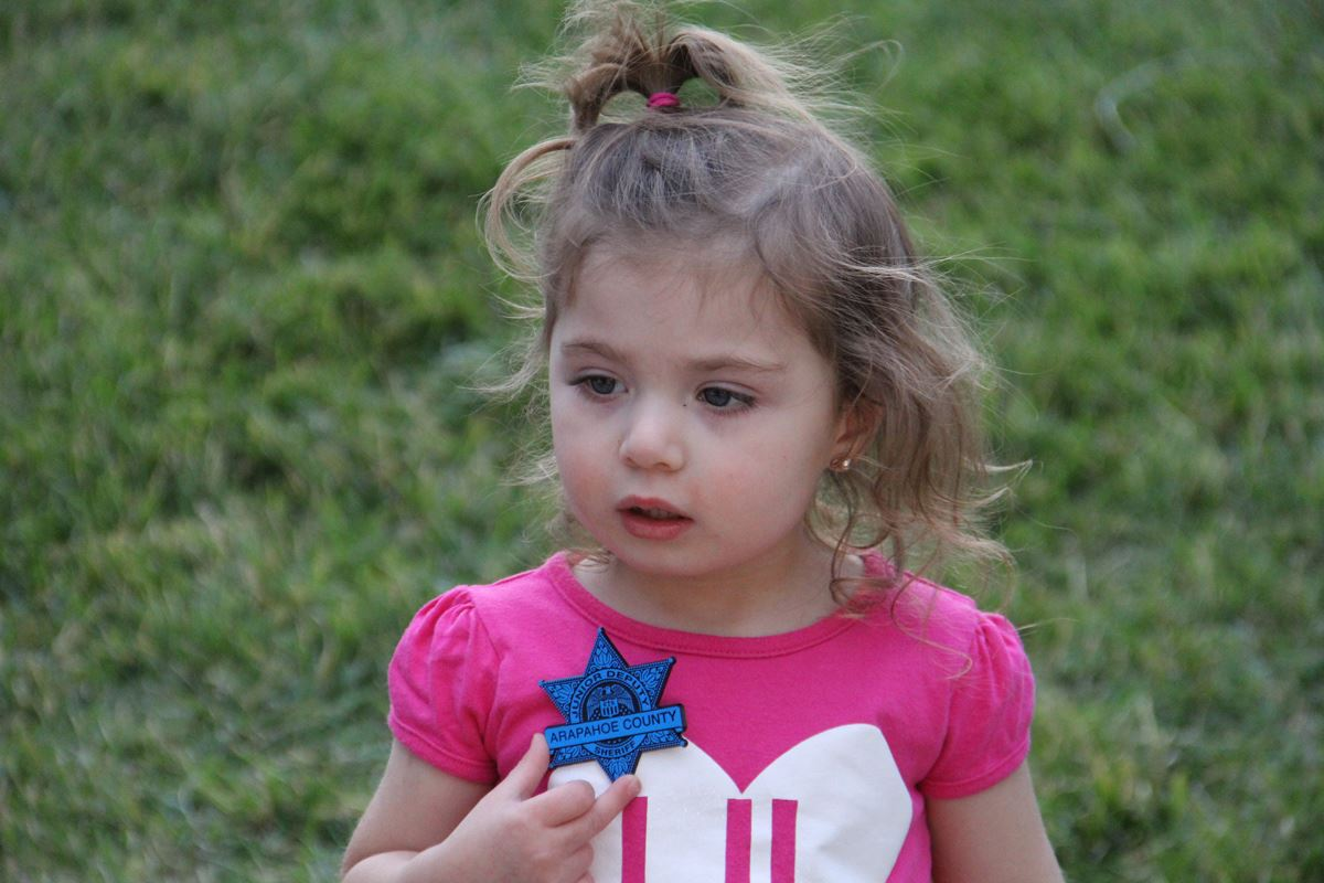 A young girl shows off her blue plastic sheriff's badge